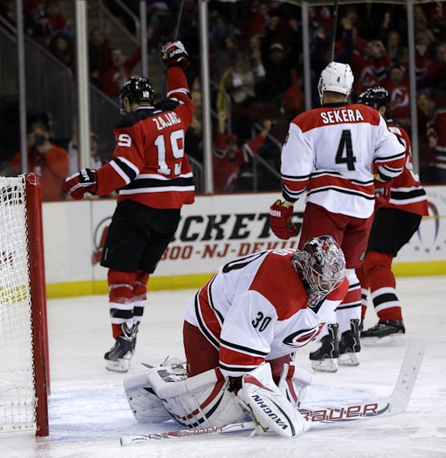 Carolina Hurricanes goalie Cam Ward, bottom, reacts after New Jersey Devils center Travis Zajac (19) scored a goal during the second period of an NHL hockey game on Wednesday, Nov. 27, 2013, in Newark, N.J. (AP Photo/Julio Cortez)