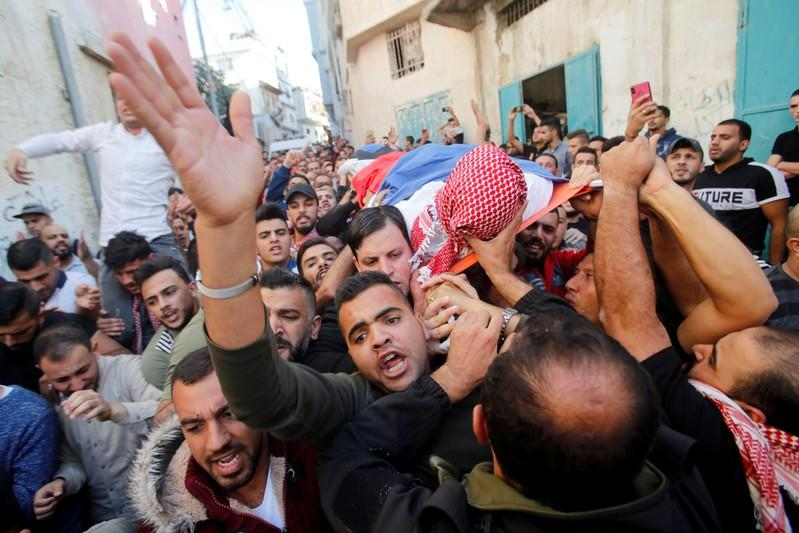 Mourners carry the body of Palestinian man Omar al-Badawi during his funeral in al-Arroub refugee camp, in the Israeli-occupied West Bank