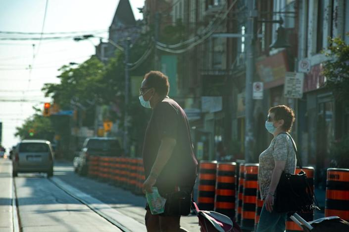 """<span class=""""element-image__caption"""">People cross the street in Toronto on Monday as the city grapples with the pandemic.</span> <span class=""""element-image__credit"""">Photograph: Stacey Newman/REX/Shutterstock</span>"""
