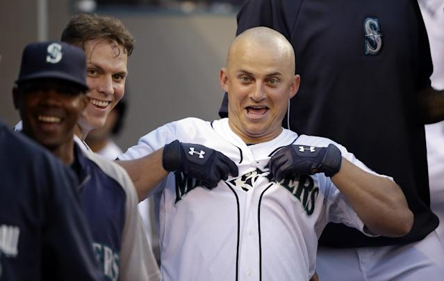 Seattle Mariners' Kyle Seager tugs at his jersey in the dugout after hitting a two-run home run against the Oakland Athletics in the fifth inning of a baseball game Saturday, July 12, 2014, in Seattle. (AP Photo/Elaine Thompson)