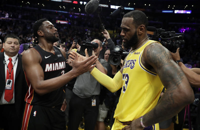Miami Heat guard Dwyane Wade, left, shakes hands with Los Angeles Lakers' LeBron James at the end of an NBA basketball game Monday, Dec. 10, 2018, in Los Angeles. (AP Photo/Marcio Jose Sanchez)