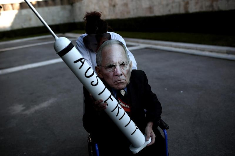 "A protester in a Wolfgang Schaeuble mask holds a syringe reading ""austerity"" at a rally outside parliament in Athens on February 15, 2015 (AFP Photo/Angelos Tzortzinis)"
