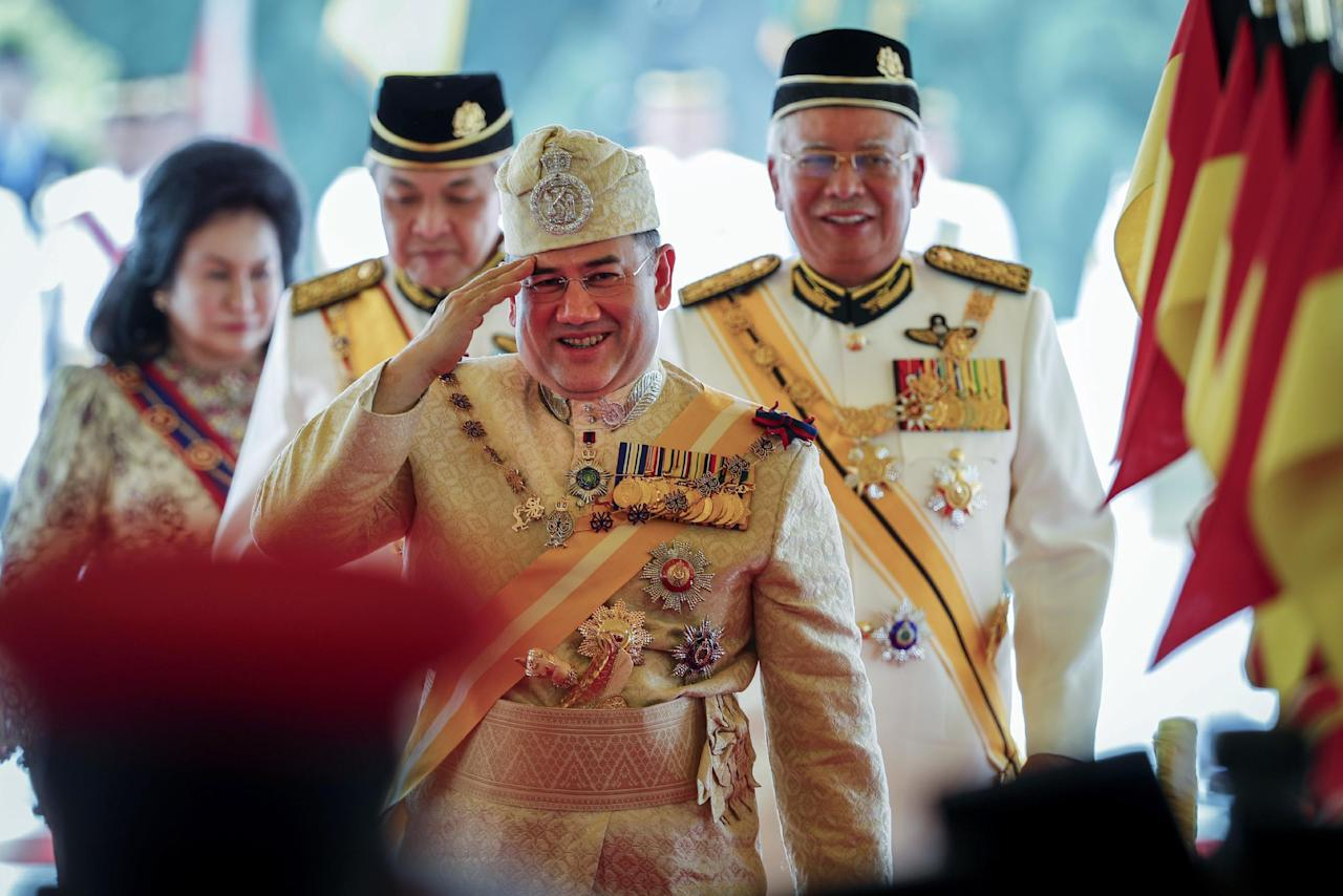 <p>Sultan Muhammad V, center, salutes after his welcome ceremony as he walks with Malaysian Prime Minister Najib Razak, right, at the Parliament House in Kuala Lumpur, Malaysia, Tuesday, Dec. 13, 2016. Sultan Muhammad V of Kelantan will serve a five-year term as King of Malaysia from Tuesday. (AP Photo/Vincent Thian) </p>