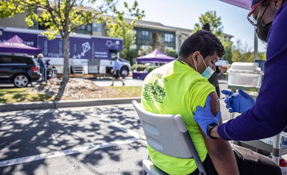 Freddy Martinez is vaccinated at Novant Health's mobile unit for COVID-19 vaccinations at Lowe's at Northlake in Charlotte, N.C., on Tuesday, April 27, 2021.