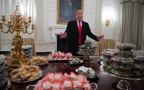 US President Donald Trump speaks alongside fast food he purchased for a ceremony honoring the 2018 College Football Playoff National Champion Clemson Tigers in the State Dining Room of the White House in Washington, DC, January 14, 2019 - Credit: SAUL LOEB/AFP