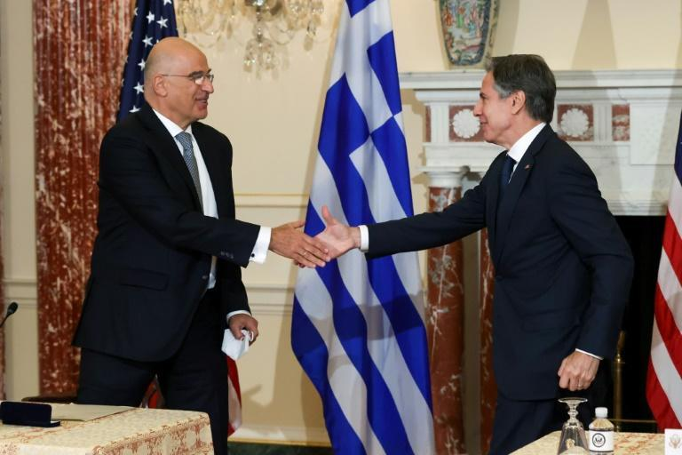 US Secretary of State Antony Blinken (R) and Greek Foreign Minister Nikos Dendias shake hands after signing the renewal of the US-Greece Mutual Defense Cooperation Agreement at the State Department (AFP/JONATHAN ERNST)