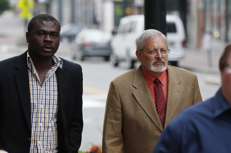 FILE - In this July 9, 2015, file photo, Michael Geilenfeld, right, arrives at U.S. Bankruptcy Court, Thursday, July 9, 2015, in Portland, Maine. An attorney says a defamation lawsuit against a Maine activist who accused an orphanage founder in Haiti of being a serial pedophile has been settled. Paul Kendrick's attorney told The Associated Press that the defendant's insurance companies agreed to pay $3 million to Hearts With Haiti but nothing to orphanage founder Michael Geilenfeld. The attorney says Hearts With Haiti and Geilenfeld dropped their defamation claims. (AP Photo/Robert F. Bukaty, File)