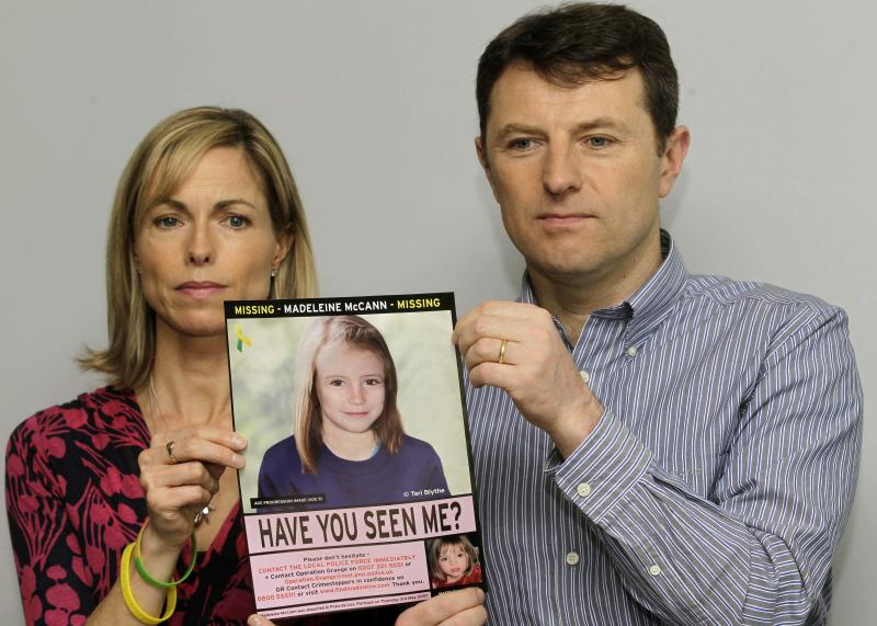 FILE - In this May 2, 2012 file photo, Kate and Gerry McCann pose for the media with a missing poster depicting an age progression computer generated image of their daughter Madeleine at nine years of age, to mark her birthday and the 5th anniversary of her disappearance during a family vacation in southern Portugal in May 2007, during a news conference in London. Portuguese prosecutors have ordered the reopening of the police investigation into the disappearance of British girl Madeleine McCann, after a review of evidence found new leads in the case, Portugal's public broadcaster and British police said Thursday Oct. 24, 2013. (AP Photo/Sang Tan, File)