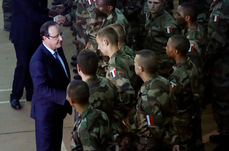 French President Francois Hollande, left, addresses the troops during a stopover from South Africa in Bangui, Central African Republic, Tuesday Dec. 10, 2013. Two French soldiers were killed in combat overnight since France stepped up its presence to restive the former French colony to help quell inter-religious violence. (AP Photo/Jerome Delay)