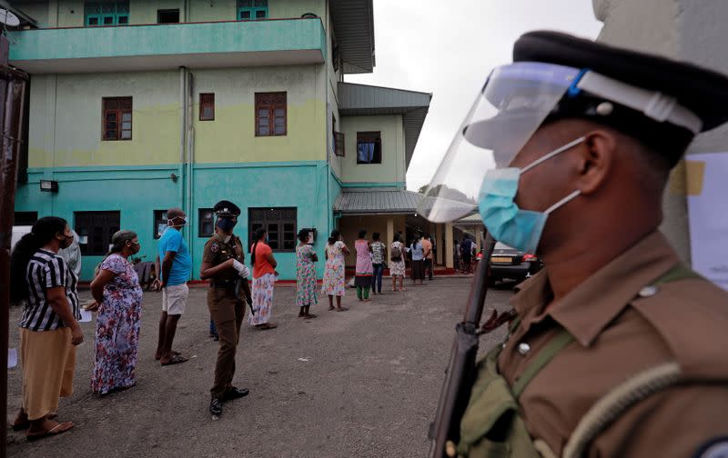 People wearing protective masks wait in a line to cast their vote outside a polling station during the country's parliamentary election in Colombo