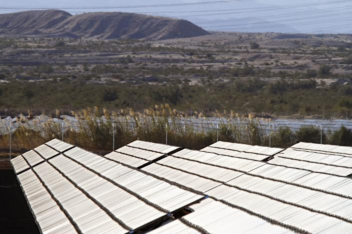 Rows of solar panels stand on desert farmland in the Imperial Valley west of El Centro, Calif.