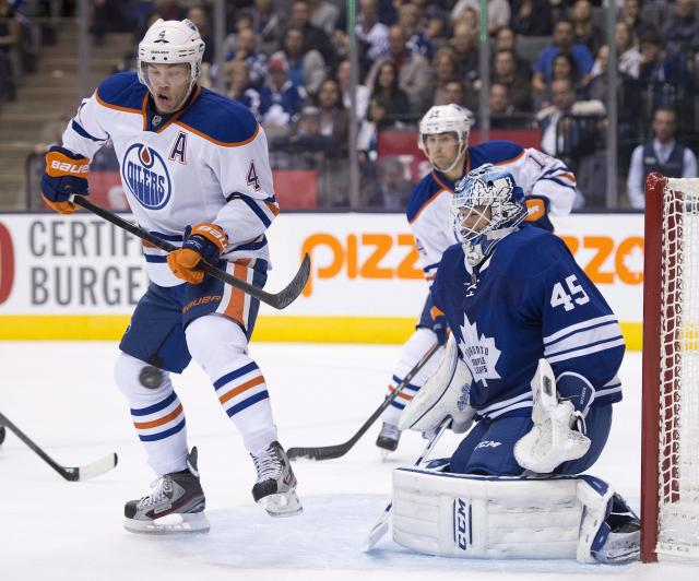 Toronto Maple Leafs goaltender Jonathan Bernier goes down to make a save as Edmonton Oilers Taylor Hall (4) tries to redirect the puck during the first period of an NHL hockey game, Saturday, Oct. 12, 2013 in Toronto. (AP Photo/The Canadian Press, Frank Gunn)
