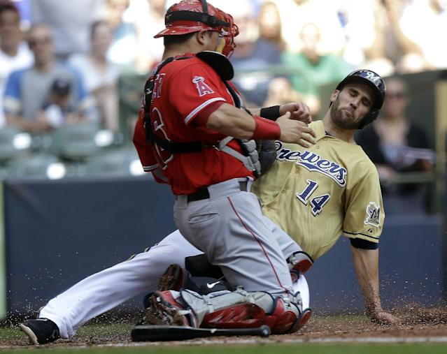 Milwaukee Brewers' Jeff Bianchi (14) slides safely past Los Angeles Angels catcher Hank Conger during the third inning of a baseball game on Sunday, Sept. 1, 2013, in Milwaukee. Bianchi scored from third on a bunt by Kyle Lohse. (AP Photo/Morry Gash)