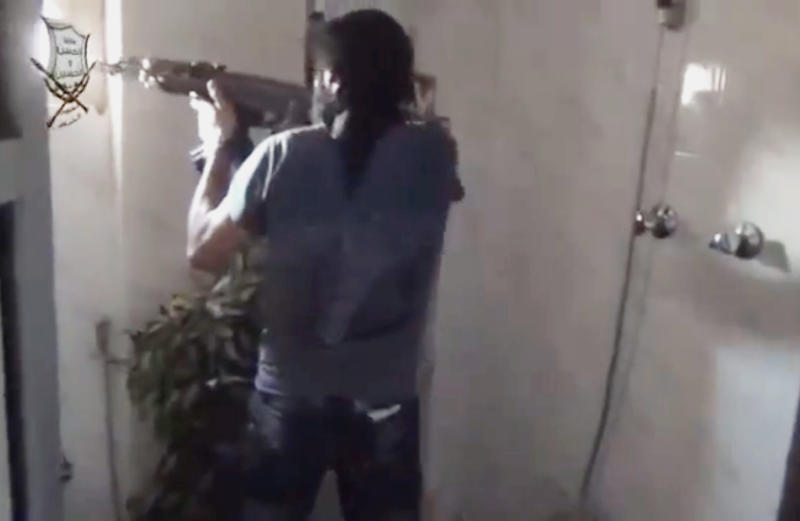 This image made from amateur video released by Ugarit News, which has been authenticated based on its contents and other AP reporting, shows a Syrian rebel firing his weapon in Damascus, Syria, Friday, June 21, 2013. The commander of Syria's rebels confirms they have received new weapons, giving his forces more power in battles against government troops and Hezbollah fighters from Lebanon. Gen. Salim Idris refused to say in an interview with Al-Jazeera TV Friday where the weapons came from. (AP Photo/Ugarit News via AP video)