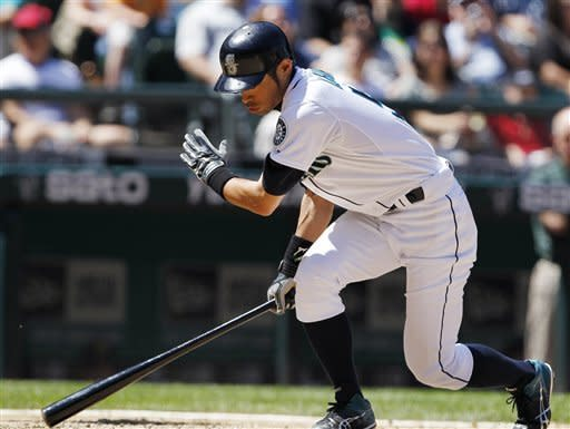 Seattle Mariners' Ichiro Suzuki spins around as he strikes out against the Oakland Athletics in the seventh inning of a baseball game Wednesday, June 27, 2012, in Seattle. (AP Photo/Elaine Thompson)