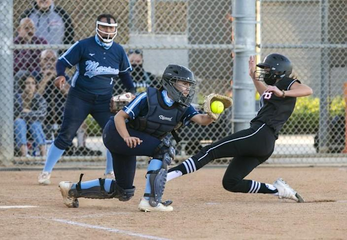 Huntington Beach's Emma Francisco beats the tag from Marina's Zoe King to score in the first inning during a Surf League softball game at Huntington Beach High School on Wednesday, April 28.