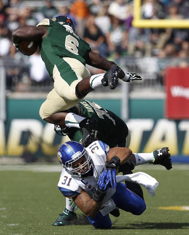 San Jose State linebacker Keith Smith, bottom, misses a tackle on Colorado State running back Chris Nwoke, top, who then runs into his offensive lineman Brandon Haynes, back, in the first quarter of an NCAA college football game in Fort Collins, Colo., on Saturday, Oct. 12, 2013. (AP Photo/David Zalubowski)