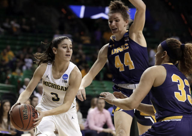 Michigan guard Katelynn Flaherty (3) works to make a pass beneath the basket as Northern Colorado center Bridget Hintz (44) and Kianna Williams (33) defend in the first half of a first-round game at the NCAA women's college basketball tournament in Waco, Texas, Friday, March 16, 2018. (AP Photo/Tony Gutierrez)