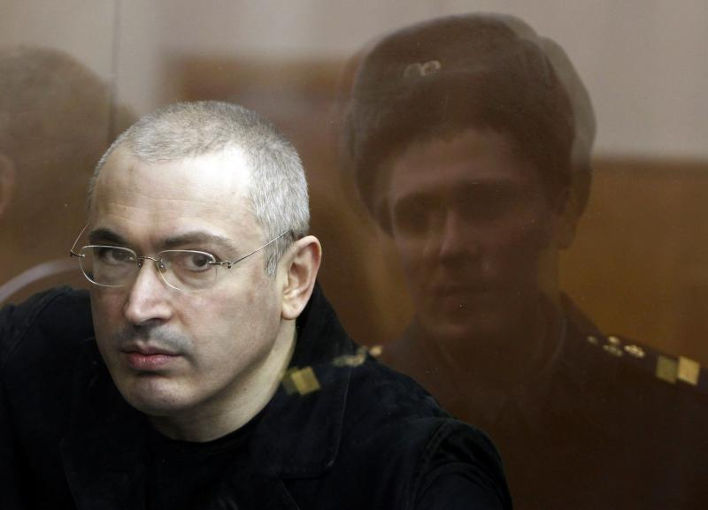 File photo of jailed Russian former oil tycoon Khodorkovsky standing in the defendants' cage during a court session in Moscow