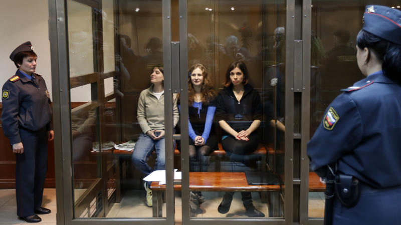 CORRECTS THE LEFTS TO RIGHT Feminist punk group Pussy Riot members, from left, Yekaterina Samutsevich, Maria Alekhina, and Nadezhda Tolokonnikova sit in a glass cage at a court room in Moscow, Wednesday. Oct. 10, 2012. Three members of the punk band Pussy Riot are set to make their case before a Russian appeals court that they should not be imprisoned for their irreverent protest against President Vladimir Putin. Their impromptu performance inside Moscow's main cathedral in February came shortly before Putin was elected to a third term. The three women were convicted in August of hooliganism motivated by religious hatred and sentenced to two years in prison. (AP Photo/Sergey Ponomarev)