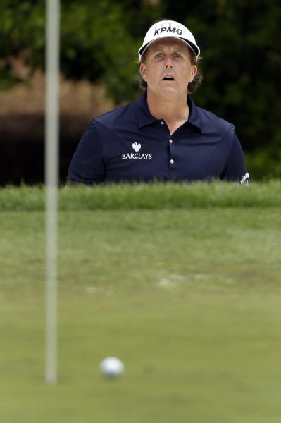 Phil Mickelson reacts as he nearly makes a shot from a sand trap on the fourth hole during the second round of the Wells Fargo Championship golf tournament at Quail Hollow Club in Charlotte, N.C., Friday, May 3, 2013. (AP Photo/Chuck Burton)