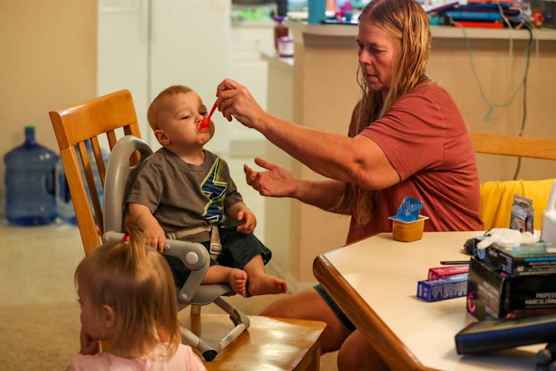 Teri's mother, Patti Armbruster, feeds one-year-old, Ash. Teri has let her daughter's large family move into her home after Oak Gregg-Donaldson, father, died hours after their seventh child was born. Their Community rallied and raised $75K and the baby is about to come home after weeks in hospital. Teri Gregg-Donaldson said the family will start therapy and they are trying to get back to their new normal as they move into her mother, Patti Armbruster's, home.