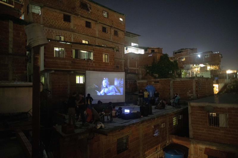 The film Aladdin is projected on a screen set up on the roof of a home in the Petare neighborhood of Caracas, Venezuela, late Monday, June 1, 2020. A neighborhood group called The Download Zone set up the movie as a free entertainment option for families cooped up since mid-March under the COVID-19 quarantine. (AP Photo/Ariana Cubillos)