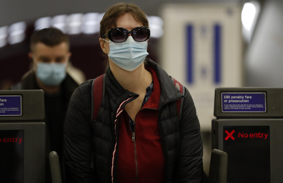 Travelers, wearing face masks, leave London's Underground Baker Street station, Tuesday, June 9, 2020. Wearing a face mask will become compulsory on the London TFL public transport service starting from June 15, 2020, as a safety measure to contrast the COVID-19 pandemic. (AP Photo/Frank Augstein)