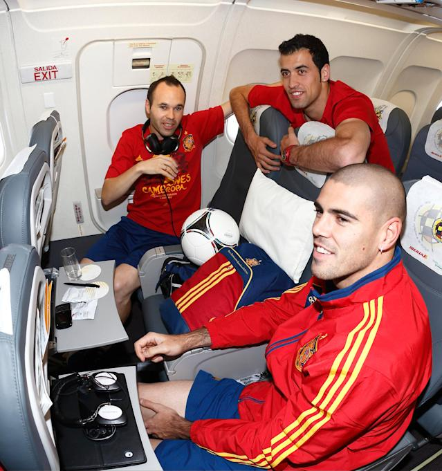 IN FLIGHT - JULY 02: In this handout image supplied by the Royal Spanish Football Federation, (L-R) Andres Iniesta, Sergio Busquets and Victor Valdes of Spain talk onboard the Spain team's airplane during their flight back to Madrid following their team's victory in the UEFA EURO 2012 final match against Italy on July 2, 2012 in flight. (Photo by Carmelo Rubio Sanchez/RFEF via Getty Images)