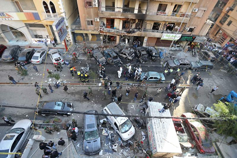 Lebanese army soldiers and forensic inspectors gather to examine the site of an explosion in the Haret Hreik area in the southern suburbs of the Lebanese capital Beirut