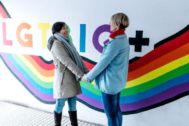 Lesbian couple hold hands and stare at each other in front of a pride flag graffiti. (Photo: Jon Vallejo via Getty Images)
