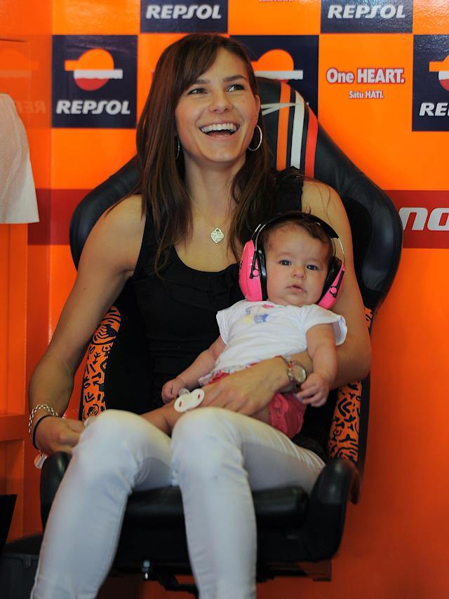 The wife of Australian rider Casey Stoner, Adriana, holds their daughter Alessandra Maria at the Catalunya racetrack in Montmelo, near Barcelona, on June 1, 2012, during the MotoGP first training session of the Catalunya Moto GP Grand Prix. AFP PHOTO/LLUIS GENELLUIS GENE/AFP/GettyImages