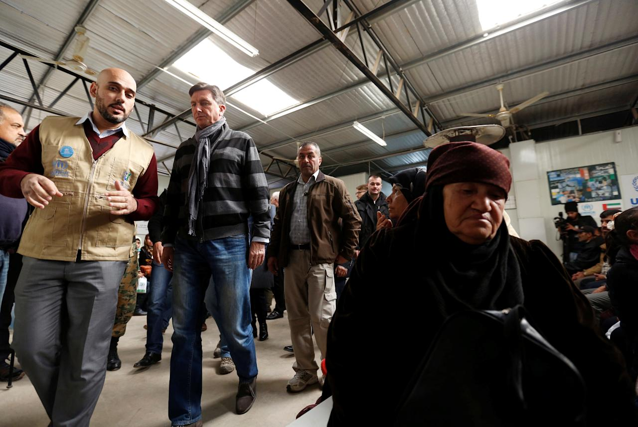 Syrian refugees wait to receive treatment at a health center, during the visit of President of Slovenia Borut Pahor (2nd L) to the refugee camp Al Zaatari in Jordan, near the border with Syria, December 3, 2016. REUTERS/Muhammad Hamed