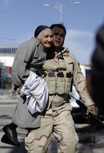 An Afghan security member carries a bystander during an attack by gunmen at a court complex in Mazar-i-sharif on April 9, 2015 (AFP Photo/Farshad Usyan)