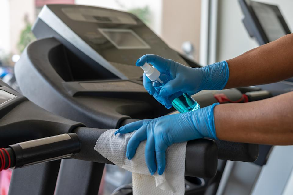 Staff using wet wipe and a blue sanitizer from the bottle to clean treadmill in gym.