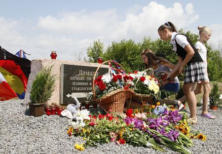 FILE PHOTO: People gather near a monument for the victims of the Malaysia Airlines flight MH17 plane crash to mark the fourth anniversary of the accident in Donetsk Region