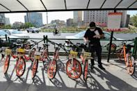 An Iranian man uses his phone to unlock a bicycle of bike-sharing service Bdood at Valiasr Square in Tehran