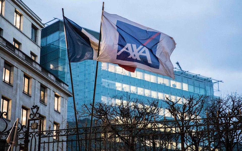 A French national flag and a flag displaying the AXA SA logo fly outside the insurance company's headquarters in Paris, France - Christophe Morin/Bloomberg