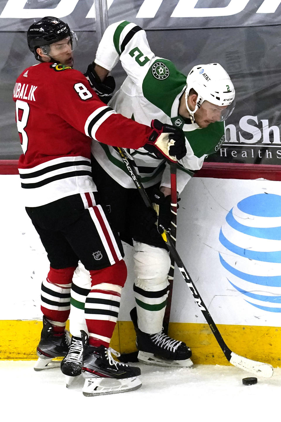Dallas Stars defenseman Jamie Oleksiak, right, works for the puck against Chicago Blackhawks left wing Dominik Kubalik during the first period of an NHL hockey game in Chicago, Sunday, May 9, 2021. (AP Photo/Nam Y. Huh)