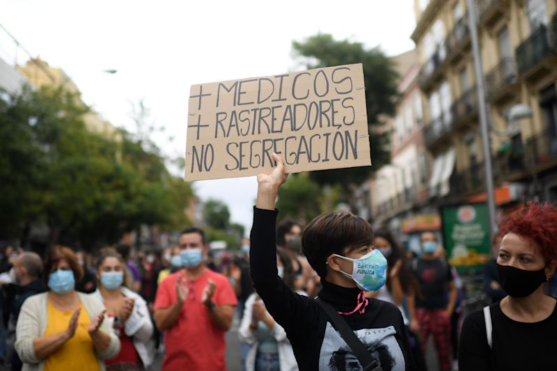"A woman holds a placard reading ""More doctors, more trakers, no segregation"" during a demonstration at the Vallecas neighborhood in Madrid, on September 20, 2020, to protest against the new restrictive measures announced by regional authorities. - The Madrid region, the epicentre of an explosion of virus infections in Spain, would place a partial lockdown on hundreds of thousands of people. Residents of the affected areas -- 858,000 or 13 percent of the 6.6 million population -- will only be allowed to leave the zone to go to work, seek medical care or take their children to school. (Photo by OSCAR DEL POZO / AFP) (Photo by OSCAR DEL POZO/AFP via Getty Images)"