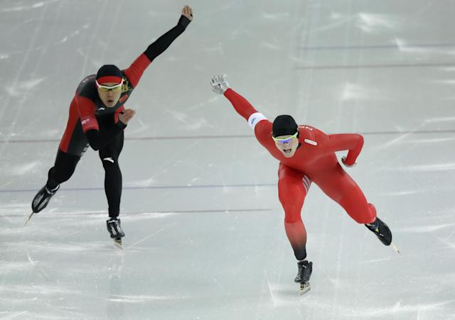 Norway's Espen Hvammen, right, and China's Tian Guojun compete in the men's 1,000-meter speedskating race at the Adler Arena Skating Center at the 2014 Winter Olympics in Sochi, Russia, Wednesday, Feb. 12, 2014. (AP Photo/David J. Phillip )