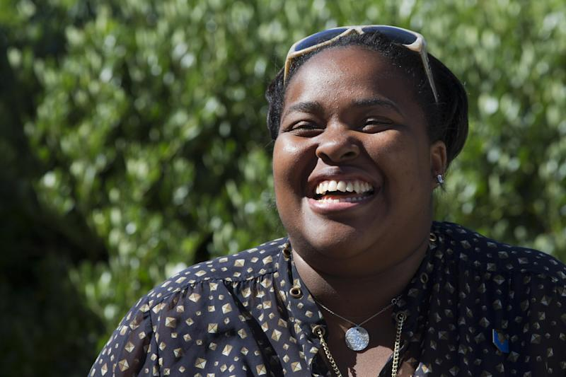 Ashley Tate-Gilmore, 29, smiles in greeting to waiting members of the media as she checks the set-up before President Barack Obama makes a statement to the media regarding events in Egypt, from his rental vacation home in Chilmark, Mass. on the island of Martha's Vineyard Thursday, Aug. 15, 2013. A large entourage of staff and press travel with President Barack Obama wherever he goes, even on an island getaway to Martha's Vineyard. And their behind-the-scenes movements are juggled by Tate-Gilmore who has been with him since his Chicago days. Tate-Gilmore heads the White House Travel Office. It's a five-person operation that handles precise logistics behind every presidential trip. (AP Photo/Jacquelyn Martin)