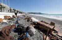 People are seen on a private beach following heavy rainfall in Nice