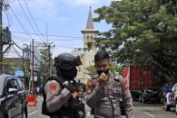 Police officers guard near a church where an explosion went off in Makassar, South Sulawesi, Indonesia, Sunday, March 28, 2021. (AP Photo/Yusuf Wahil)