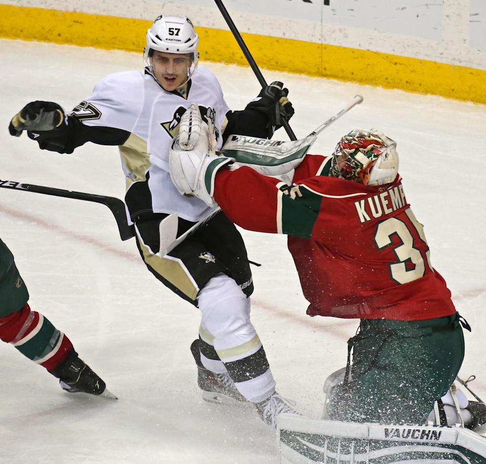Pittsburgh Penguins' Marcel Goc, left, of Germany, and Minnesota Wild goalie Darcy Kuemper crash together during the first period of an NHL hockey game, Tuesday, Nov. 4, 2014, in St. Paul, Minn. (AP Photo/Bruce Bisping)