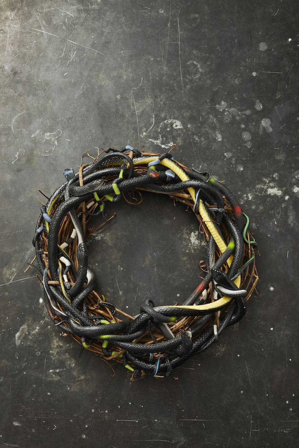 """<p>Your neighbors will get a kick out of this snake wreath, which is simple enough to make all on your own. Just glue a variety of plastic snakes directly onto a wreath form made of twigs to achieve the look. </p><p><a class=""""link rapid-noclick-resp"""" href=""""https://go.redirectingat.com?id=74968X1596630&url=https%3A%2F%2Fwww.orientaltrading.com%2Fvinyl-realistic-snakes-a2-39_9600.fltr&sref=https%3A%2F%2Fwww.goodhousekeeping.com%2Fholidays%2Fhalloween-ideas%2Fg32948621%2Fhalloween-door-decorations%2F"""" rel=""""nofollow noopener"""" target=""""_blank"""" data-ylk=""""slk:SHOP TOY SNAKES"""">SHOP TOY SNAKES</a></p>"""