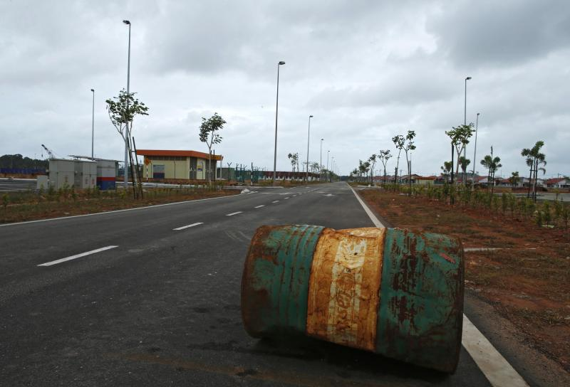 A rusty oil barrel lies in the middle of a road in the largely empty new township built for workers of the Pengerang Integrated Petroleum Complex in Pengerang