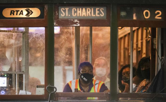 A masked conductor rolls along South Carrollton Ave. in New Orleans, Tuesday, Aug. 3, 2021. (David Grunfeld/The Times-Picayune/The New Orleans Advocate via AP)