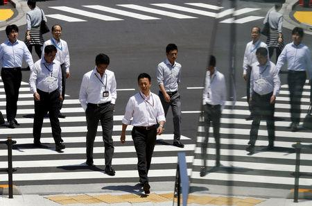 FILE PHOTO: Office workers are reflected in a glass railing as they cross a street during lunch hour in Tokyo June 1, 2015.  REUTERS/Thomas Peter/File Photo