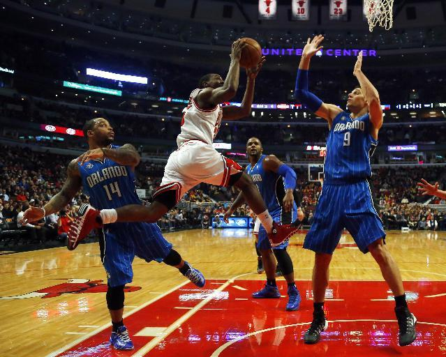 Chicago Bulls point guard Marquis Teague, center, shoots between Orlando Magic point guard Jameer Nelson, left, and center Nikola Vucevic, right, as Magic forward Glen Davis, back, is near during the first half of an NBA basketball game in Chicago, Monday, Dec. 16, 2013. (AP Photo/Jeff Haynes)